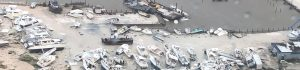 "In this image courtesy of US Coast Guard Air Station Clearwater, boats are strewn across a marina in the Bahamas on September 2, 2019, as Hurricane Dorian makes its way across the Bahamas. - Dorian crept towards the southeast coast of the US on September 3, 2019, weakening slightly but remaining a dangerous storm after leaving a trail of death and destruction in the Bahamas. At least five deaths have been reported in the Bahamas from a storm which Prime Minister Hubert Minnis called a ""historic tragedy"" for the Atlantic archipelago.The Miami-based National Hurricane Center said Dorian, which has dumped as much as 30 inches (76 centimeters) of rain on the Bahamas, had been downgraded from a Category 3 to a Category 2 storm on the five-level wind scale. (Photo by HO / US Coast Guard / AFP) / RESTRICTED TO EDITORIAL USE - MANDATORY CREDIT ""AFP PHOTO / US COAST GUARD"" - NO MARKETING NO ADVERTISING CAMPAIGNS - DISTRIBUTED AS A SERVICE TO CLIENTS"